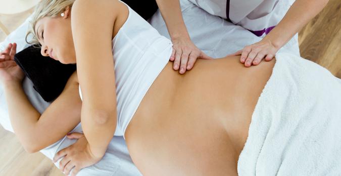 Une femme enceinte reçoit un massage dans un contexte de massothérapie prénatale