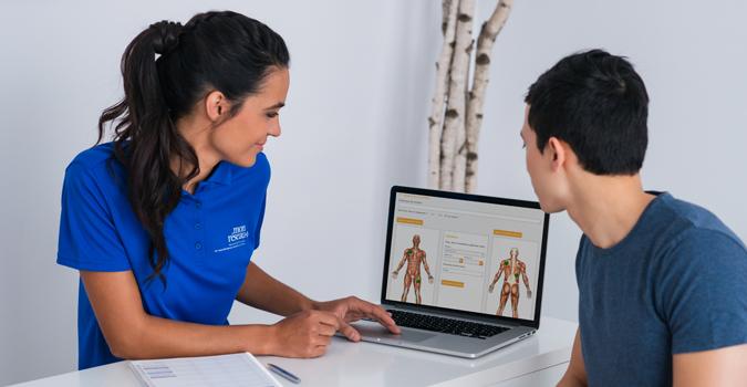 Un massothérapeute discute avec un client en lui montrant son dossier numérique afin de rédiger un rapport d'interventions.