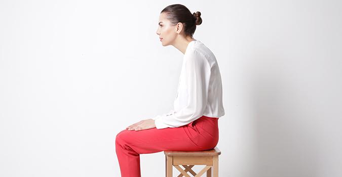 Jeune femme de profil ayant la tête et le cou débalancés vers l'avant liée à une protraction cervicale.